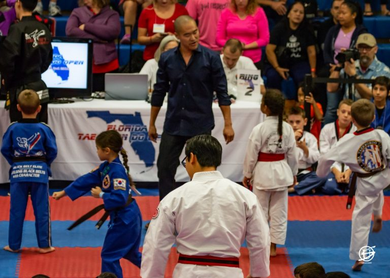 man watches as children compete in tae kwon do forms tournament