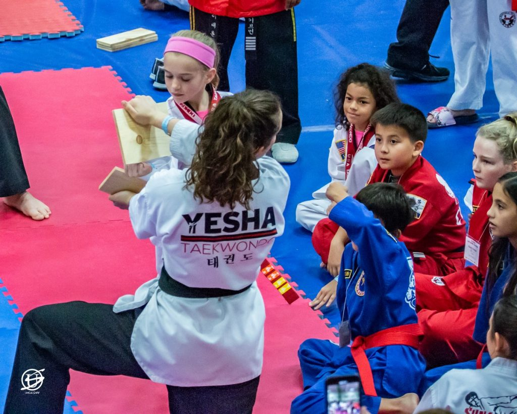 young girl punching a board held by a woman and breaking it