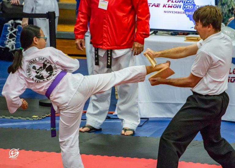 side view of tae kwon do girl kicking and breaking a board held by a young man