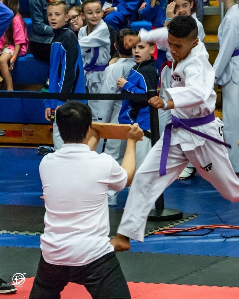 young man dressed in tae kwon do uniform lunging toward a board in order to break it