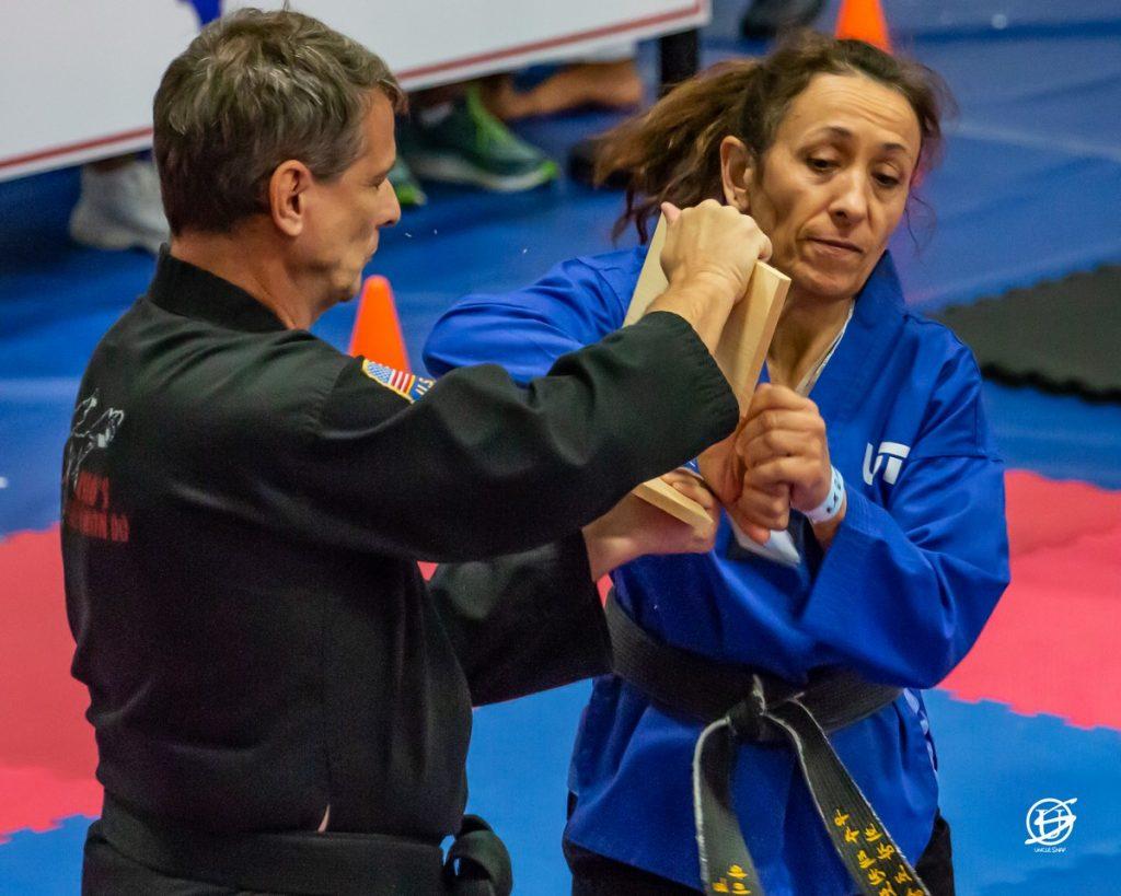 female tae kwon do competitor breaking a board