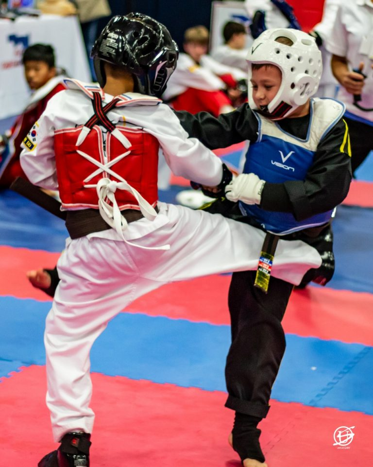 two uniformed boys sparring in tae kwon do tournament
