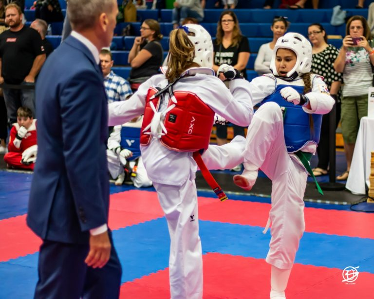 two uniformed girls sparring in tae kwon do tournament