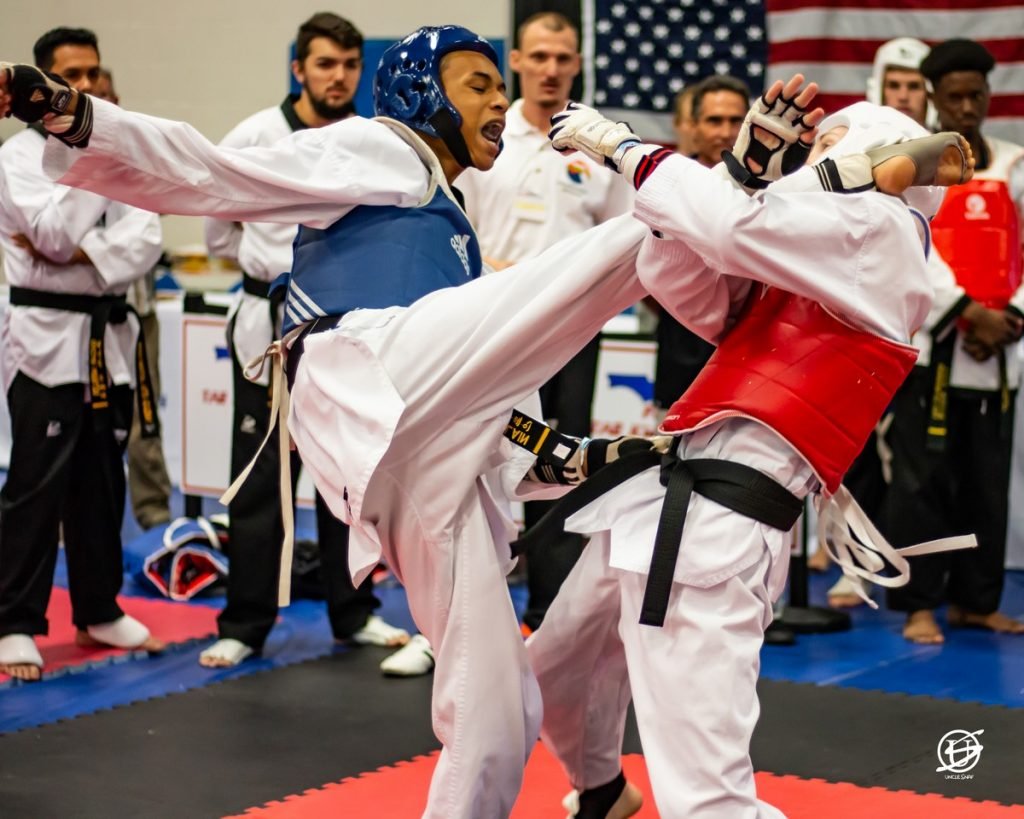 two uniformed young men sparring in tae kwon do tournament