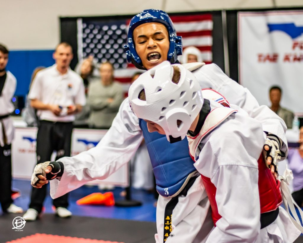 close up of two uniformed young men sparring in tae kwon do tournament