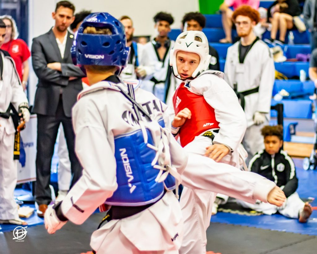 two uniformed competitors sparring in tae kwon do tournament