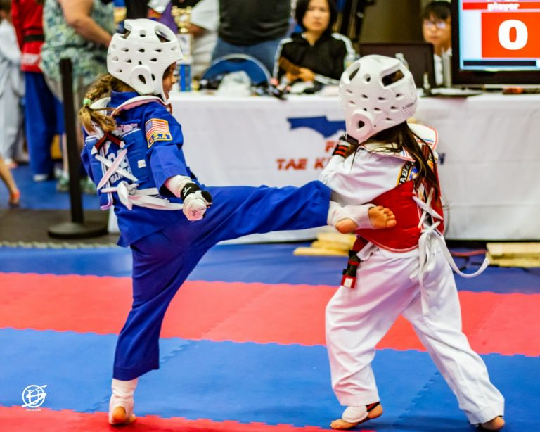 two uniformed young girls sparring in tae kwon do tournament