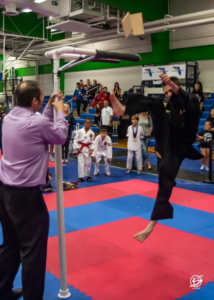 Young male competitor in tae kwon do tournament performing a high kick