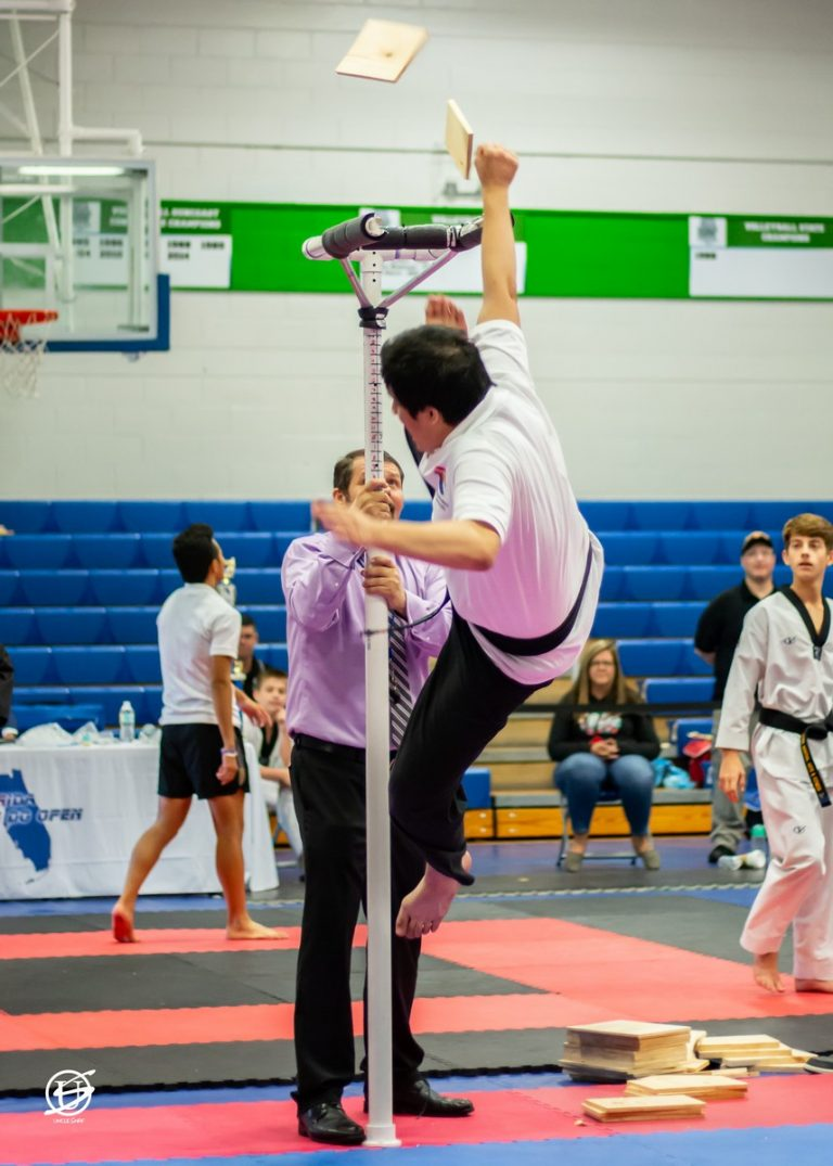 Young male competitor in tae kwon do tournament performing kicking a board off a high stand