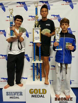 three boys standing on podest with trophies and cash